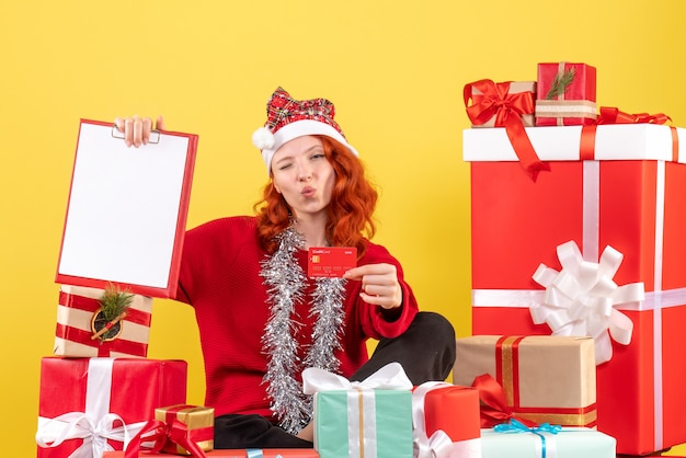 Front view of young woman sitting around xmas presents holding bank card on a yellow wall