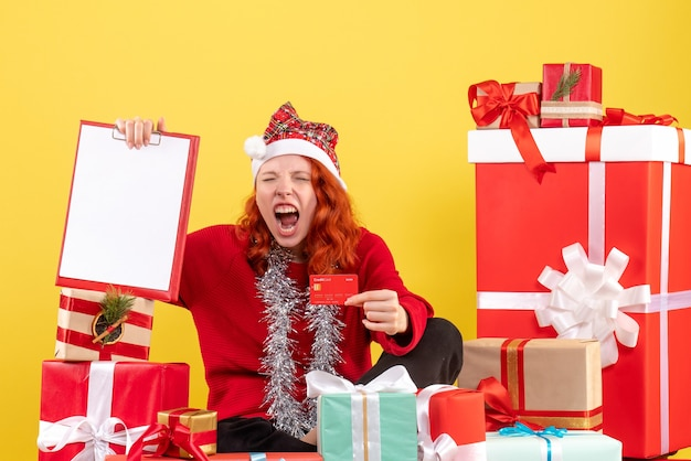 Front view of young woman sitting around xmas presents holding bank card on the yellow wall