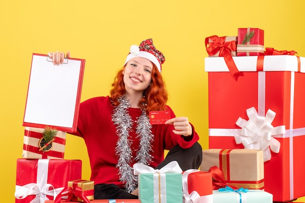 Front view of young woman sitting around xmas presents holding bank card on yellow wall