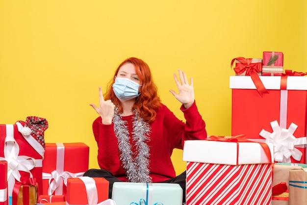 クリスマスの周りに座っている正面図若い女性は黄色の背景にマスクでプレゼント新年ウイルス感情covid-color