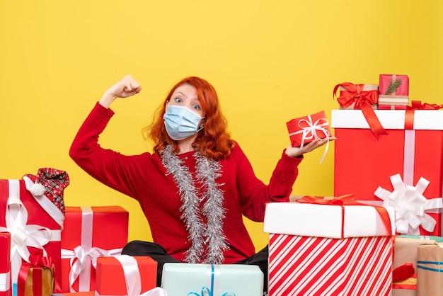黄色のマスクでクリスマスプレゼントの周りに座っている正面図若い女性