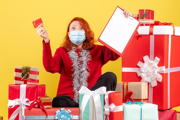 Front view of young woman sitting around xmas presents in mask with bank card on a yellow wall