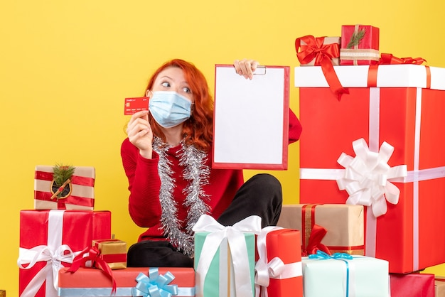 Front view of young woman sitting around xmas presents in mask with bank card on the yellow wall