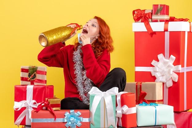 Vista frontale della giovane donna seduta intorno ai regali di natale in maschera con champagne sulla parete gialla