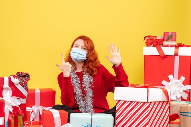 Vista frontale della giovane donna seduta intorno ai regali di natale in maschera su sfondo giallo nuovo anno virus emozione covid- colore