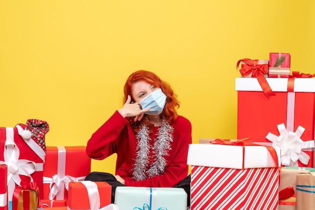 Vista frontale della giovane donna seduta intorno ai regali di natale in maschera su sfondo giallo nuovo anno virus emozioni covid- colore