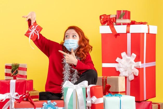Vista frontale della giovane donna seduta intorno a regali di natale in maschera su una parete gialla