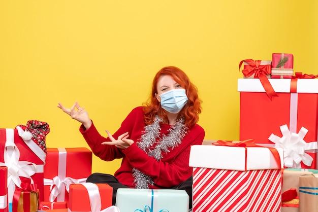 Giovane donna di vista frontale che si siede intorno ai regali di natale nella maschera su colore giallo