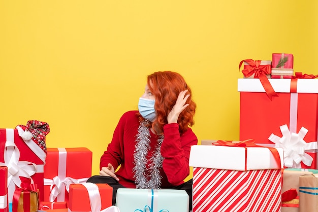 Front view young woman sitting around xmas presents in mask on yellow