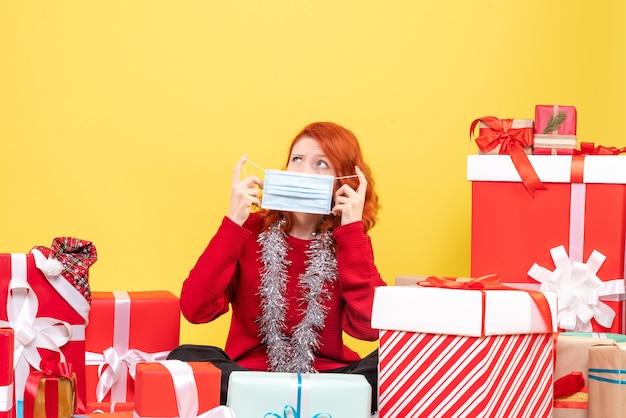 크리스마스 주위에 앉아 전면보기 젊은 여자는 노란색에 마스크를 쓰고 선물