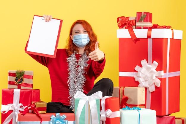 Вид спереди молодая женщина, сидящая вокруг рождественских подарков с файловой заметкой на желтом