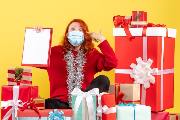 Вид спереди молодая женщина, сидящая вокруг рождественских подарков с файловой заметкой о вирусе желтых эмоций, цвет covid- новый год