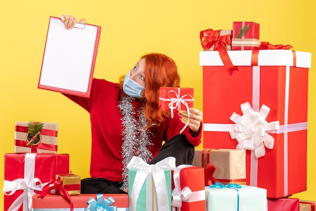 크리스마스 주위에 앉아있는 전면보기 젊은 여자가 노란색 감정 바이러스 covid- 새해 색상에 파일 메모와 함께 선물