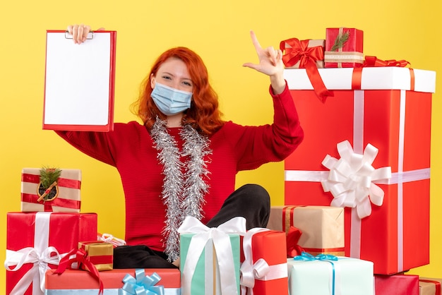 Вид спереди молодая женщина, сидящая вокруг рождественских подарков с заметкой о желтом вирусе, эмоции covid - новогодний цвет
