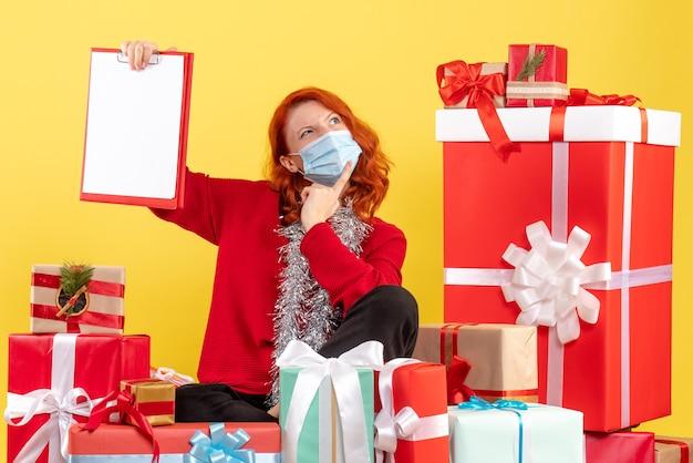 Вид спереди молодая женщина, сидящая вокруг рождественских подарков с файловой заметкой