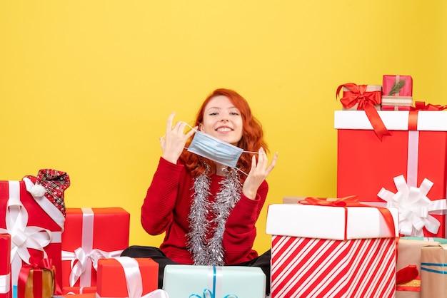 Вид спереди молодая женщина, сидящая вокруг рождественских подарков с маской на желтом новогоднем вирусе covid- color
