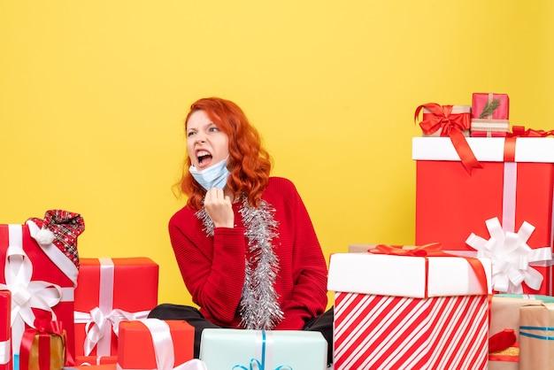 クリスマスの周りに座っている正面図の若い女性は、黄熱病の感情covid-新年の色にマスクを提示