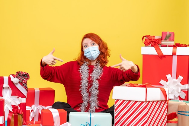 クリスマスの周りに座っている正面図若い女性は黄色のマスクを提示 無料写真