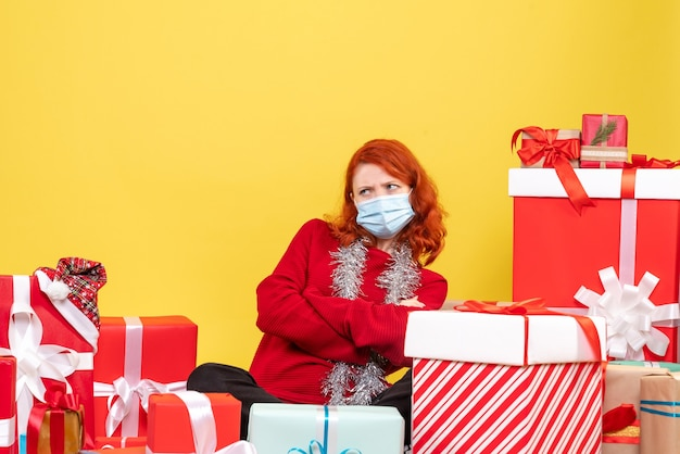 クリスマスの周りに座っている正面図若い女性は黄色い新年の感情covid-colorウイルスのマスクを提示します