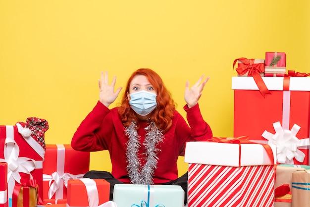 Вид спереди молодая женщина, сидящая вокруг рождественских подарков с маской на желтом вирусе, эмоции covid- новогодний цвет