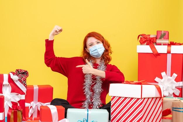 Вид спереди молодая женщина, сидящая вокруг рождественских подарков с маской на желтом
