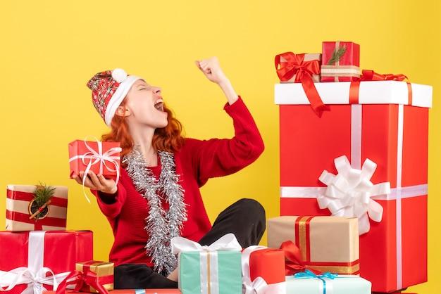 Vista frontale della giovane donna seduta intorno ai regali di natale sulla parete gialla