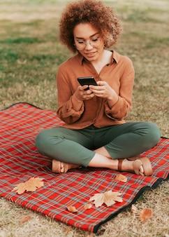 彼女の電話をチェックしながらピクニック毛布の上に座っている正面の若い女性