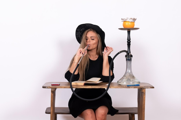 Front view of young woman sitting and smoking hookah on white wall