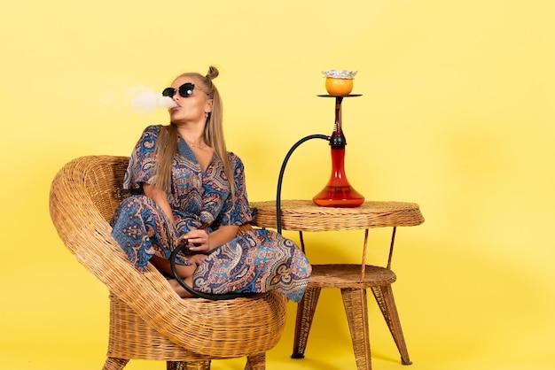 Vista frontale della giovane donna seduta e fumante narghilè sulla parete gialla