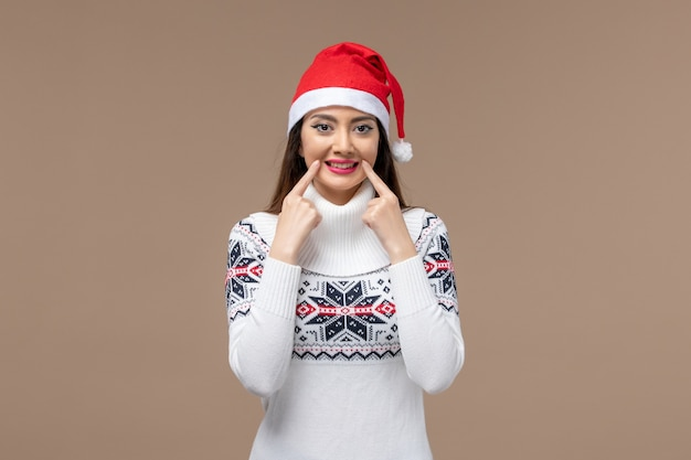 Front view young woman smiling on brown background emotion christmas new year