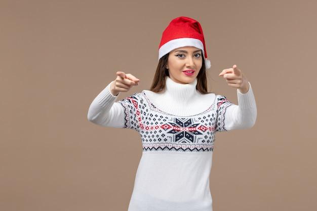 Вид спереди молодая женщина улыбается на коричневом фоне эмоции рождество новый год