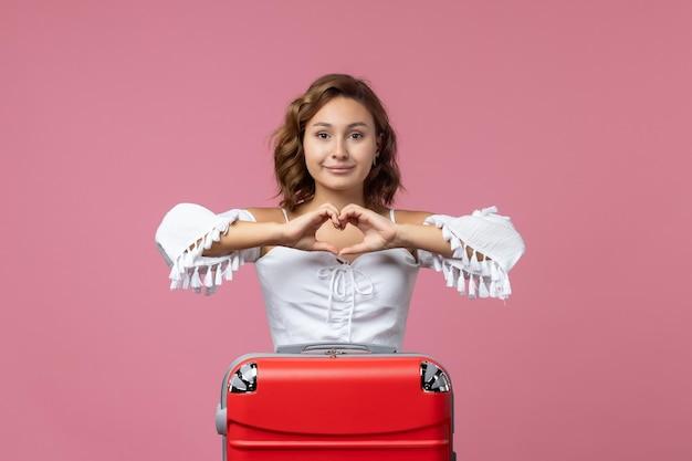 Vista frontale della giovane donna che sorride e si prepara per il viaggio con la borsa rossa sul muro rosa