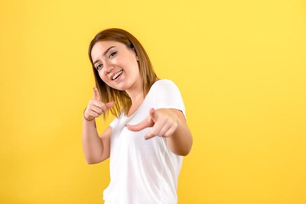 Vista frontale della giovane donna sorridente sulla parete gialla