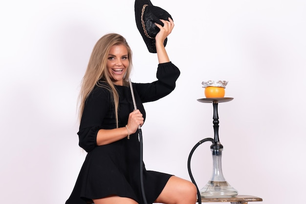 Front view of young woman smoking hookah on a white wall