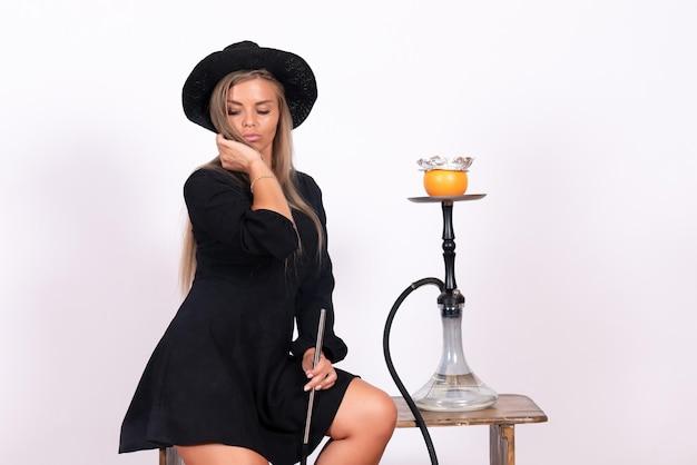 Vista frontale della giovane donna che fuma narghilè sul muro bianco