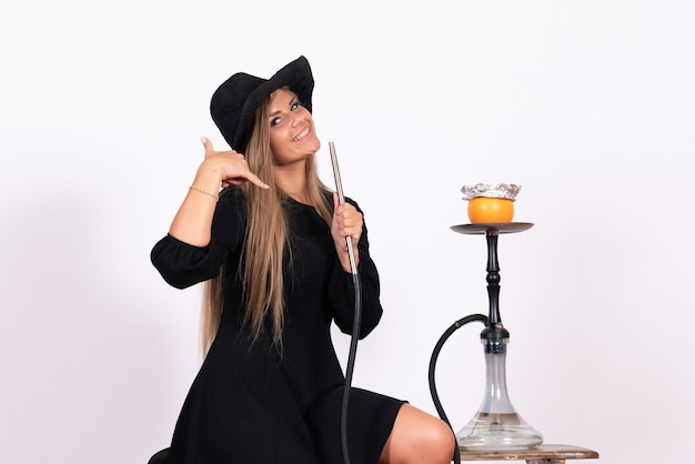 Front view of young woman smoking hookah on white wall