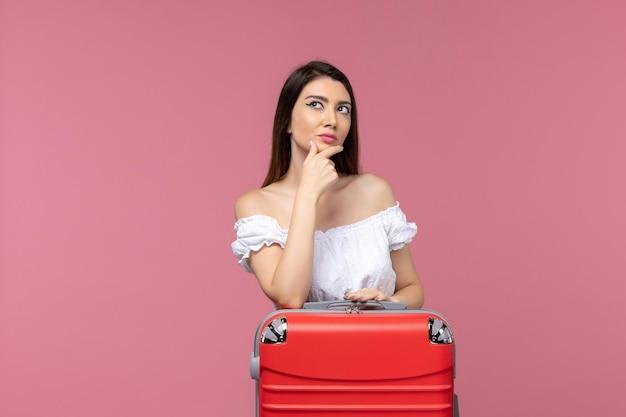 正面図若い女性が立って、淡いピンクの背景の旅で休暇の準備をしています海外海外航海の旅