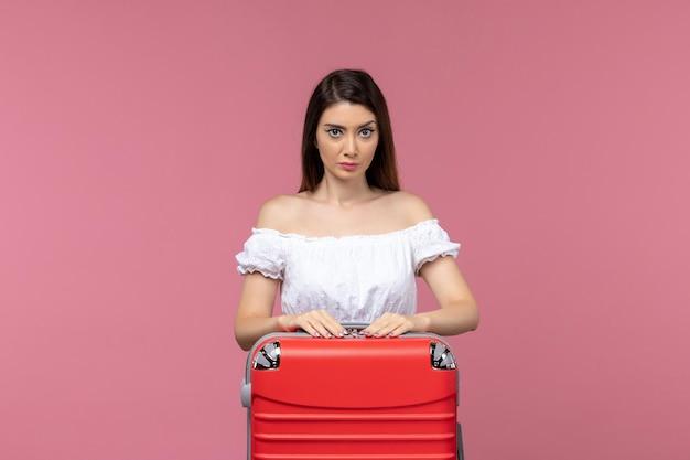핑크 데스크 여행 해외 해외 여행 바다 여행에 서서 휴가를 준비하는 전면보기 젊은 여자