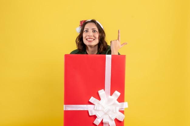 Vista frontale della giovane donna in piedi all'interno della scatola e sorridente sul muro giallo