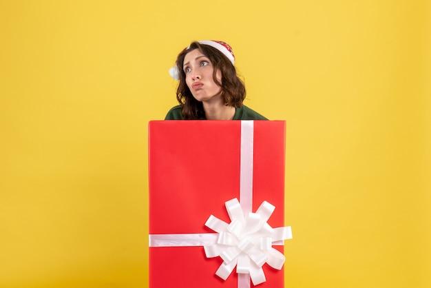 Vista frontale della giovane donna in piedi all'interno della scatola sulla parete gialla
