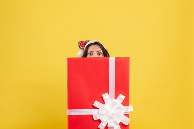 Front view of young woman standing inside box on yellow wall