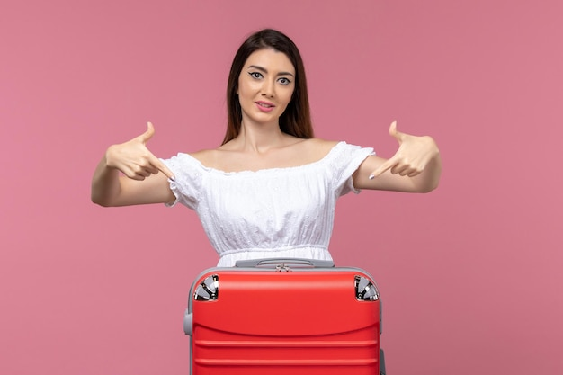 Front view young woman standing and preparing for vacation on the pink background journey sea trip abroad overseas voyage