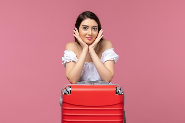 Front view young woman standing and preparing for vacation on pink desk journey sea trip woman abroad vacation