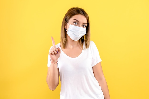 Front view of young woman in sterile mask on yellow wall