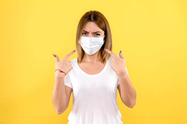 Vista frontale della giovane donna in maschera sterile sulla parete gialla