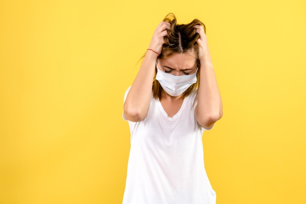 Front view of young woman stressed on yellow wall