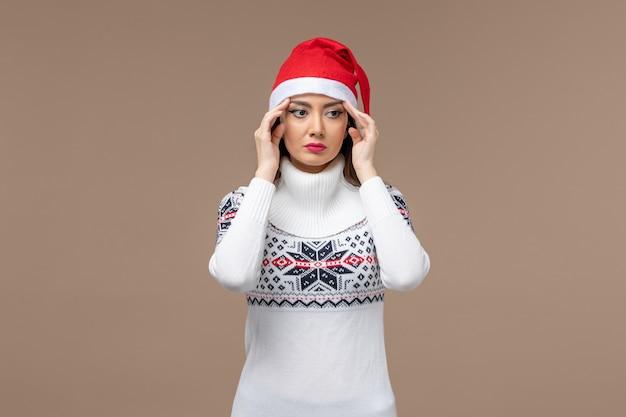 Вид спереди молодая женщина, напряженно думая на коричневом фоне, новогодние эмоции, рождество