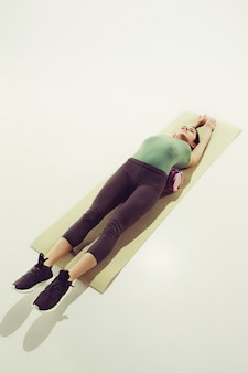 Front view of a young woman stretching body in gymnastics class.