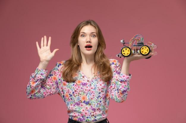 奇妙な車のおもちゃのデザインに驚いた正面図若い女性