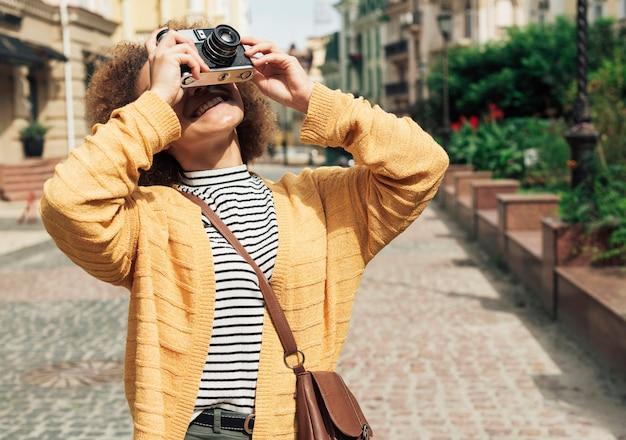 Молодая женщина, делающая фото с камерой, вид спереди